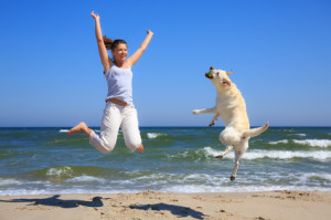 Woman and dog breed Labrador jumping on the beach